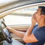 A man yawning while driving