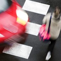 Pedestrian accident about to happen with moving car and crossing pedestrian