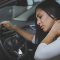 Female driver rubbing her aching neck after long drive