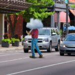 Extremely distracted cell phone using man is unknowingly walking out into city traffic jaywalking causing traffic problems; stupidity illustrated by man having his head in the clouds.