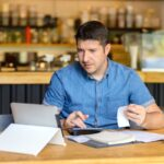 Mature new small business owner calculating online restaurant bill expenses and taxes