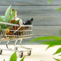 Supermarket trolley with marijuana leafs and medical cannabis oil cbd on wooden backdrop