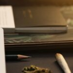 Jar of cannabis buds, gold lid, notebooks, joint on black background